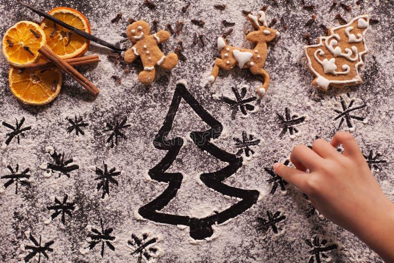 儿童手图画在面粉的假日场面为做准备 库存照片