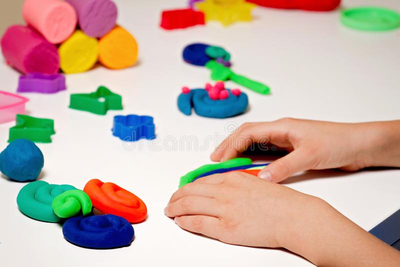 儿童手工造型雕塑黏土或彩色塑泥在白色桌上 免版税图库摄影