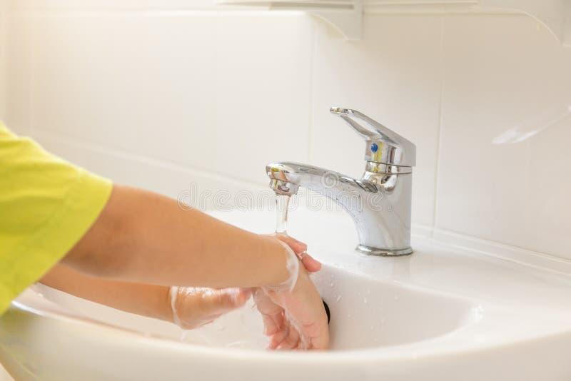 儿童手被洗在卫生间水槽的淌淌水下 免版税库存图片