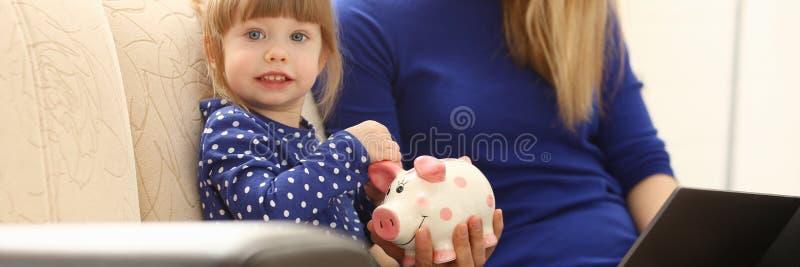 儿童投入硬币的小女孩胳膊在piggybank 免版税库存图片