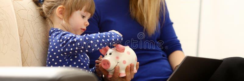 儿童投入硬币的小女孩胳膊在piggybank 库存图片