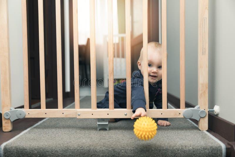 儿童投掷的球通过在台阶前面的安全门 免版税库存照片