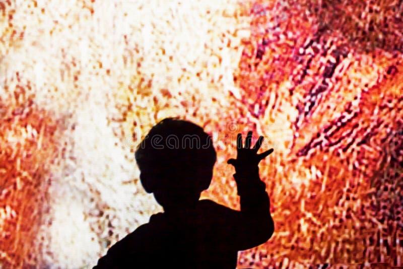 儿童接触大屏幕 儿童在色的玻璃的手接触 免版税库存图片