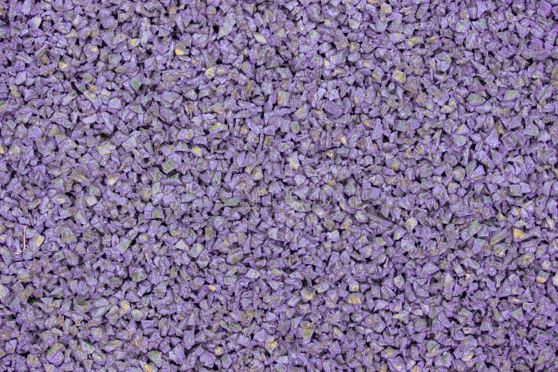 儿童操场的淡紫色紫罗兰色橡胶涂层 构造颗粒状背景 体育健身比赛的室外楼面料 免版税库存照片