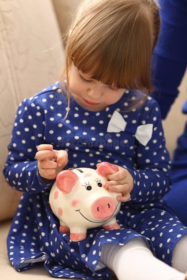 儿童放硬币的小女孩胳膊入piggybank 免版税库存图片