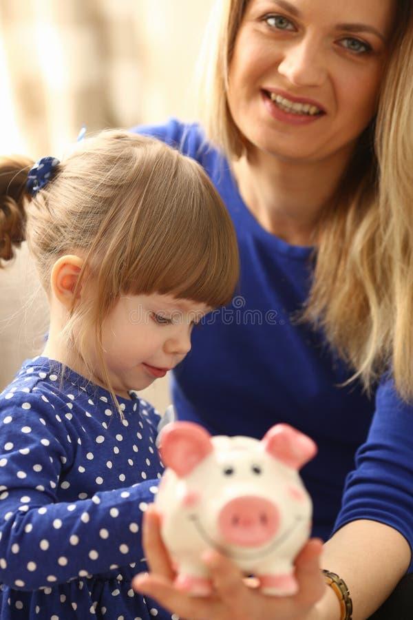 儿童放硬币的小女孩胳膊入piggybank 免版税图库摄影