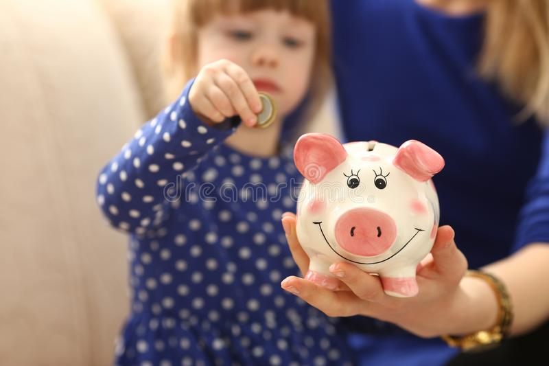 儿童放硬币的小女孩胳膊入piggybank 免版税库存照片