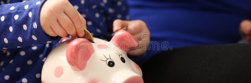 儿童放硬币的小女孩胳膊入piggybank 库存照片