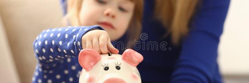 儿童放硬币的小女孩胳膊入piggybank 库存图片