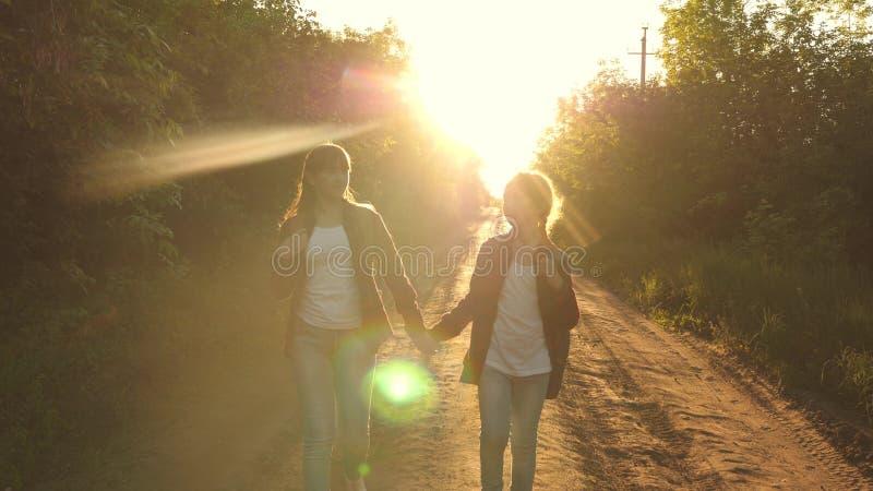 儿童旅客 青少年的女孩旅行并且握手 r 有背包的女孩是在的乡下公路 免版税库存图片
