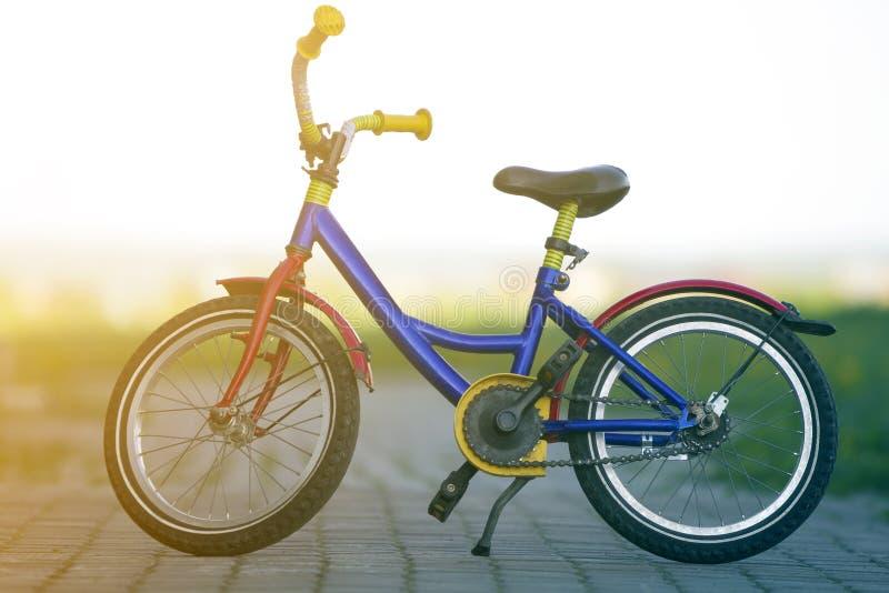 儿童明亮的多彩多姿的蓝色,黄色和红色自行车特写镜头在旁边立场留给支持在空的被铺的街道中部  库存图片