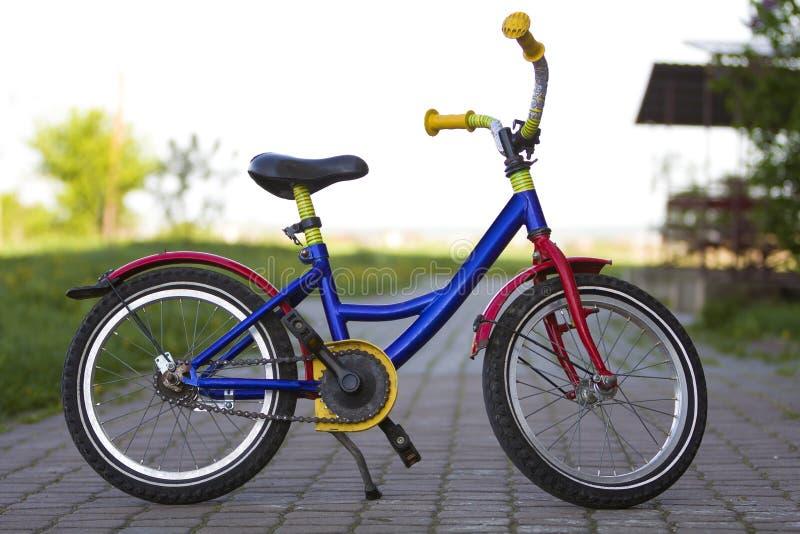 儿童明亮的多彩多姿的蓝色,黄色和红色bicyc特写镜头  库存图片