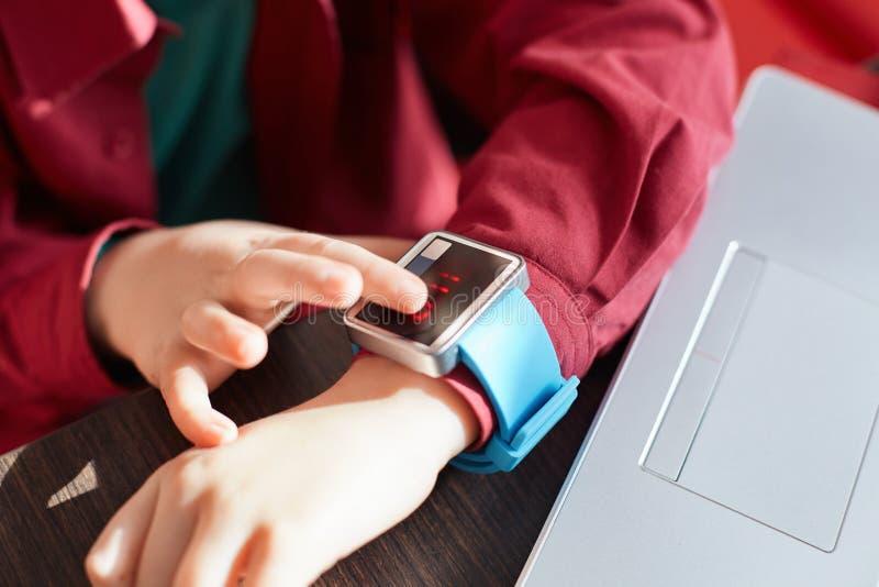 儿童有巧妙的手表的` s手特写镜头  感人的电子手表 便携的小配件概念 显示时间 使用smartwatch w 库存图片