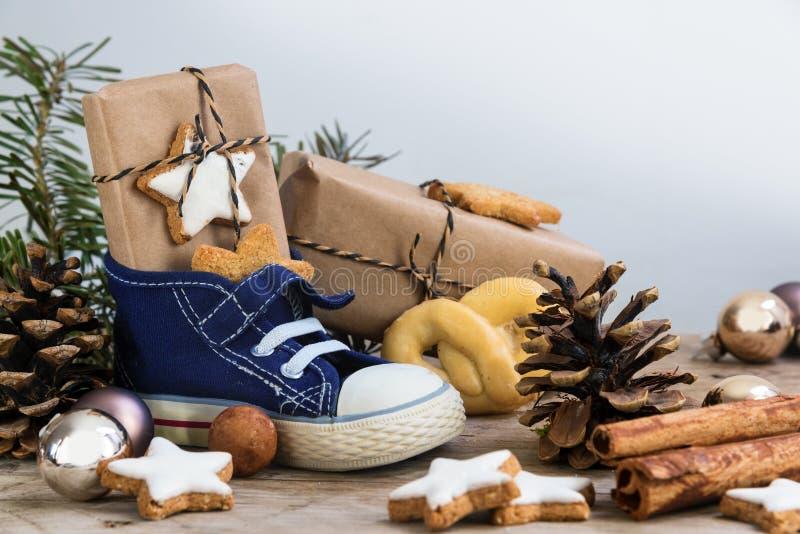 儿童有甜点、礼物和圣诞节装饰品的` s鞋子在ru 免版税图库摄影