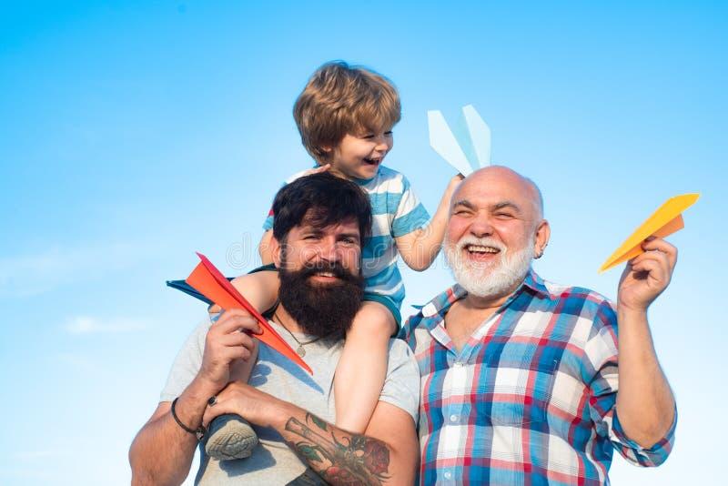 儿童有纸飞机梦想的飞行员飞行员旅行 父亲节-祖父、父亲和儿子拥抱和 免版税库存照片