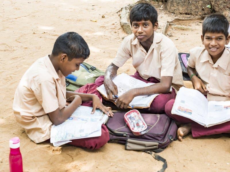 儿童朋友学习与书的男孩同学坐地板室外在学校操场 免版税库存照片