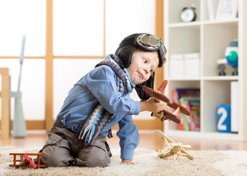 儿童梦想和想象力概念 使用与木飞机的可爱的小男孩 图库摄影