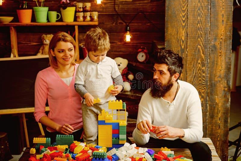 儿童概念 与砖玩具的儿童游戏 有母亲的小孩和父亲建立与五颜六色的块的结构 免版税图库摄影