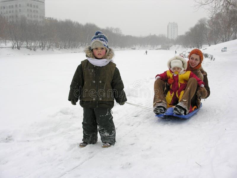儿童母亲雪撬冬天 免版税库存图片