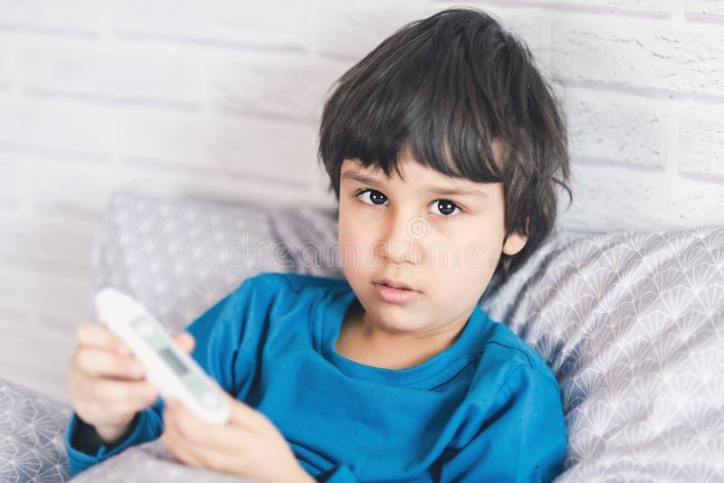 儿童流感病残,有医疗温度计的男孩在嘴,健康病症 与冷的鼻炎的孩子,变凉 免版税库存图片