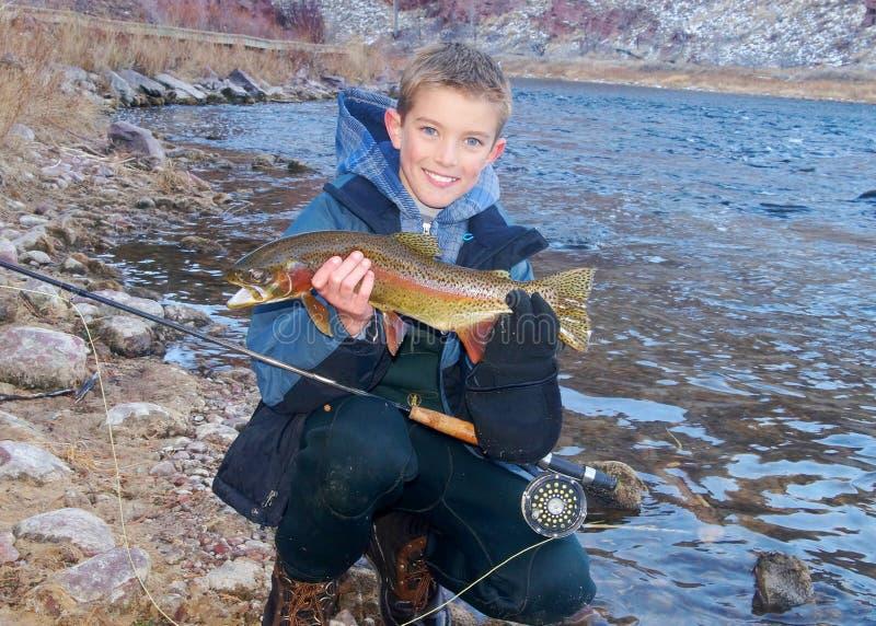 儿童渔-拿着战利品鳟鱼 免版税图库摄影