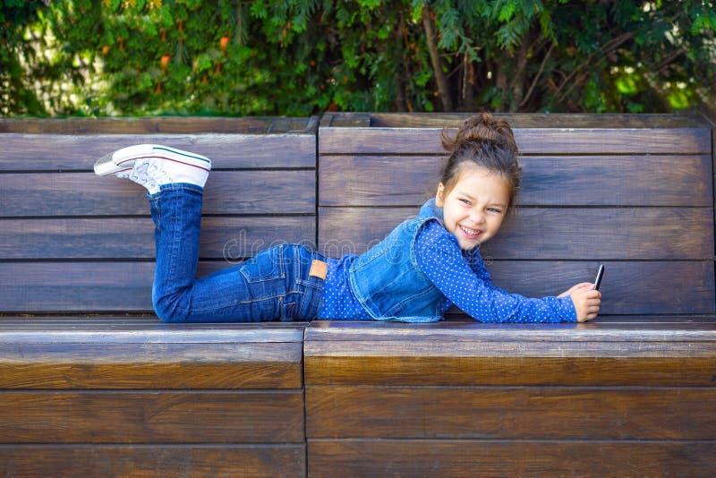 儿童游戏一个电话和微笑在户外咖啡馆 库存图片