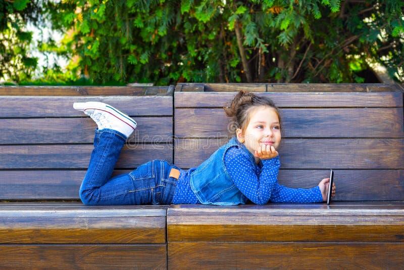 儿童游戏一种片剂和微笑在户外咖啡馆 童年 免版税图库摄影