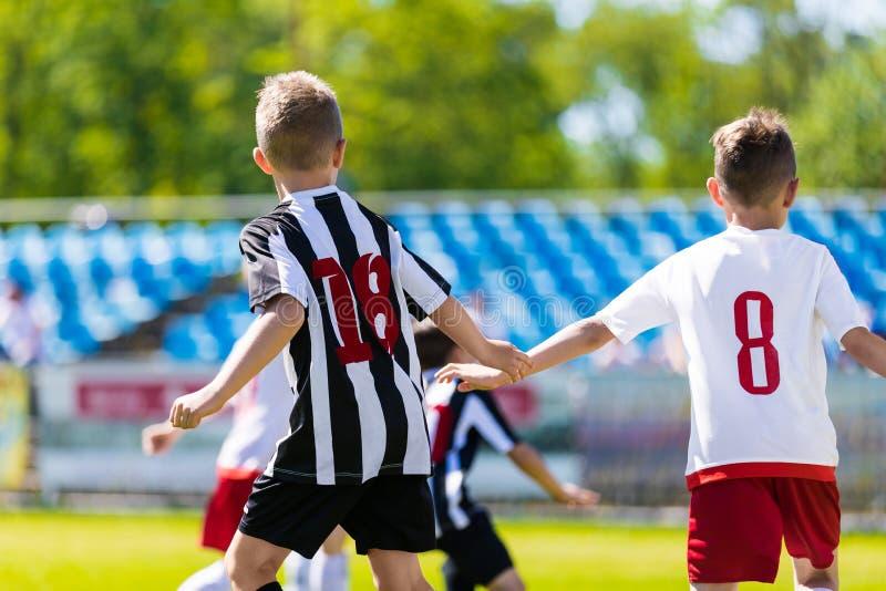 儿童游戏体育 踢足球比赛的孩子 踢在绿草沥青的年轻男孩足球 库存照片