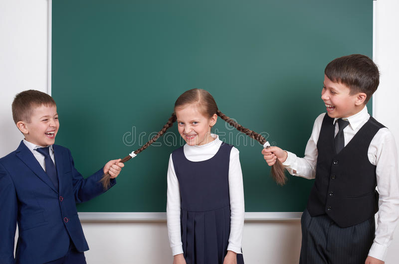 儿童游戏和有乐趣,男孩在空白的学校黑板背景附近拉扯女孩辫子,穿戴在经典黑衣服, grou 免版税库存图片