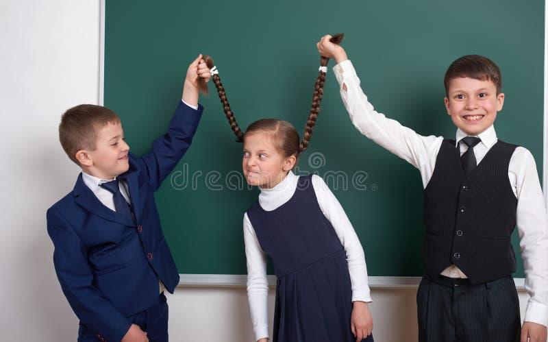 儿童游戏和有乐趣,男孩在空白的学校黑板背景附近拉扯女孩辫子,穿戴在经典黑衣服, grou 库存图片