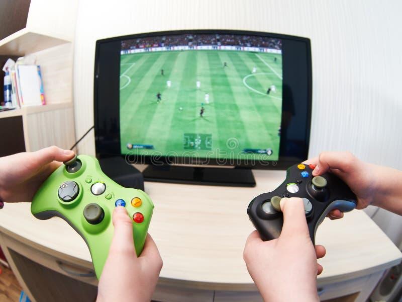 儿童游戏在踢橄榄球的比赛控制台 免版税图库摄影