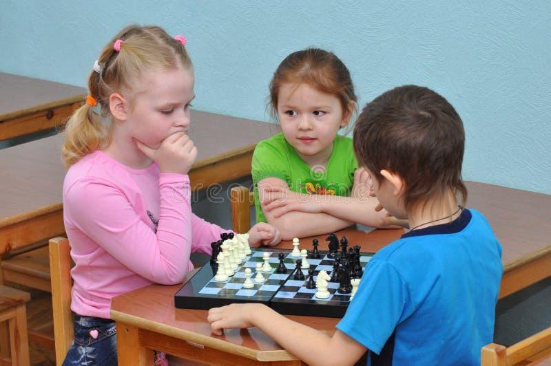 儿童游戏棋在幼儿园小组的一张桌上 免版税库存照片