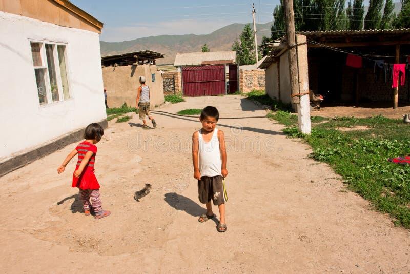 儿童游戏比赛在一个晴朗的村庄庭院里 免版税库存照片