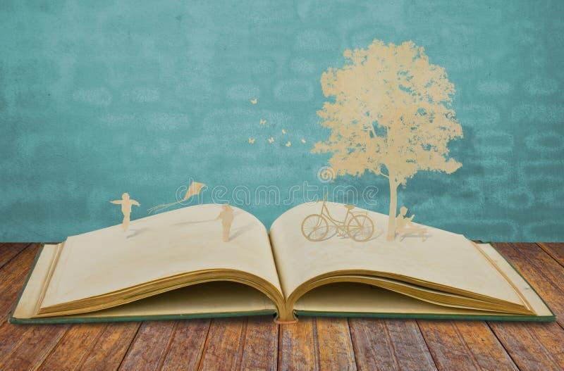 儿童游戏纸裁减在旧书的 库存图片