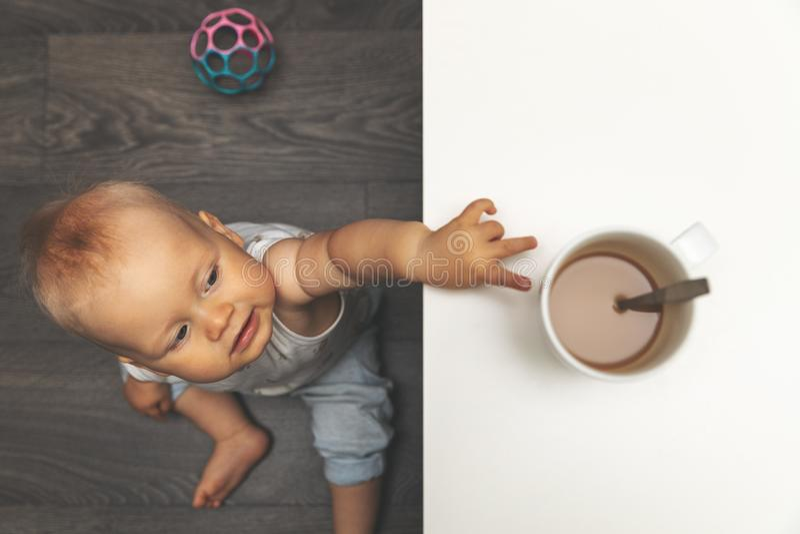 儿童烧伤和烫伤伤害概念-到达为在桌上的热的饮料杯子的小男孩 免版税图库摄影