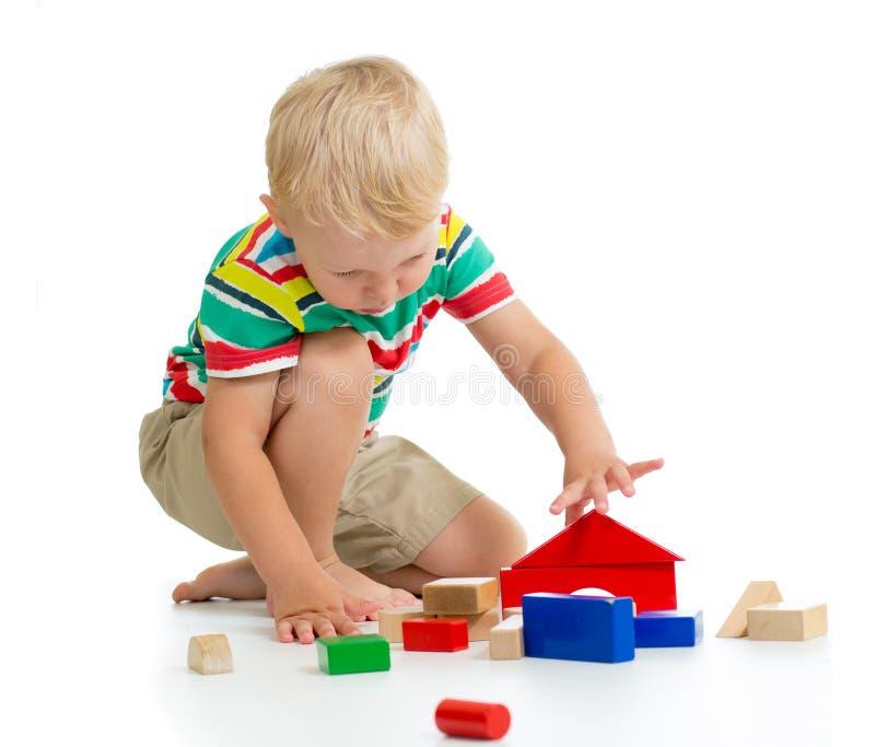 儿童男孩与五颜六色的木立方体的大厦城堡 免版税库存图片