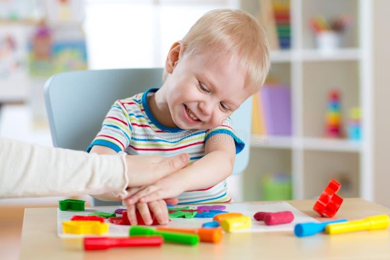 儿童男孩使用用黏土面团、教育和托儿概念 免版税库存照片