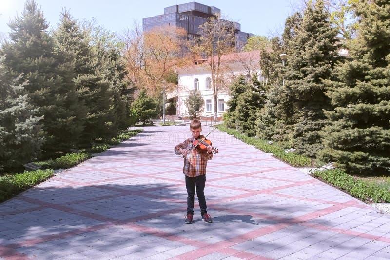 儿童男孩在城市播放在胡同的小提琴身分在街道上 免版税库存照片