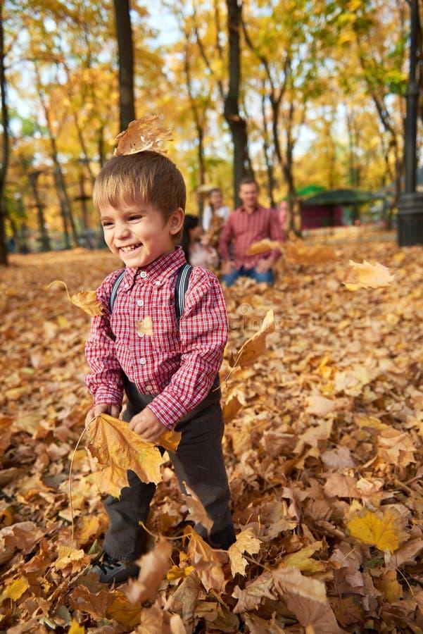 儿童男孩在秋天有他的家庭的城市公园 明亮的黄色树 免版税库存图片