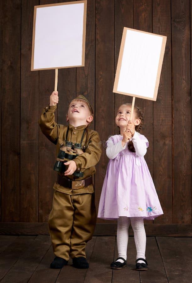 儿童男孩打扮作为减速火箭的军服和女孩的战士桃红色礼服的 他们关于拿着空白的海报的`退伍军人的 库存图片