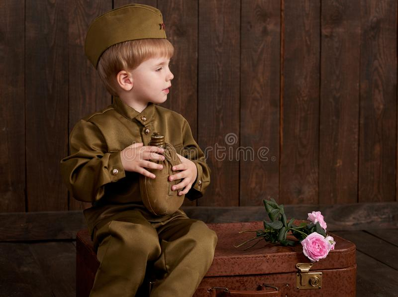 儿童男孩打扮作为减速火箭的军服的战士有烧瓶的坐老手提箱,黑暗的木背景,减速火箭的猪圈 免版税库存照片