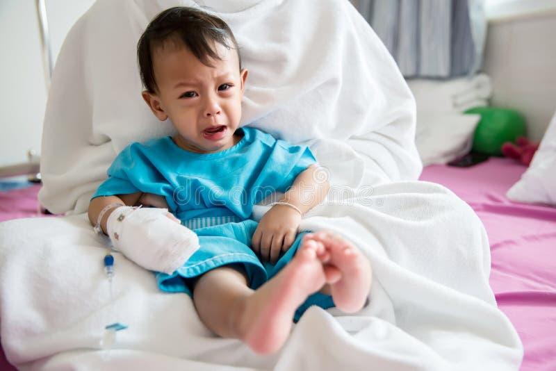 儿童病症 贴在静脉内管的小婴孩患者的手在医院病床上 小病残和哭泣在妈妈 库存图片