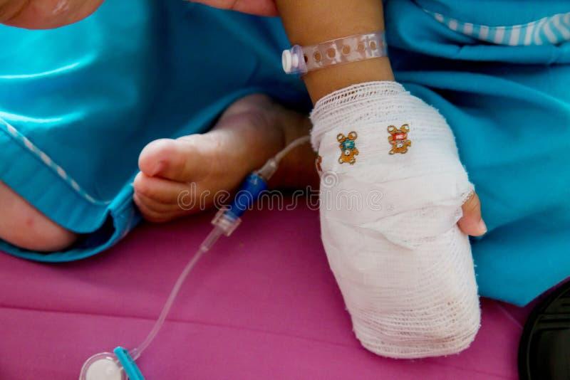 儿童病症 贴在静脉内管的小婴孩患者的手在医院病床上 库存照片