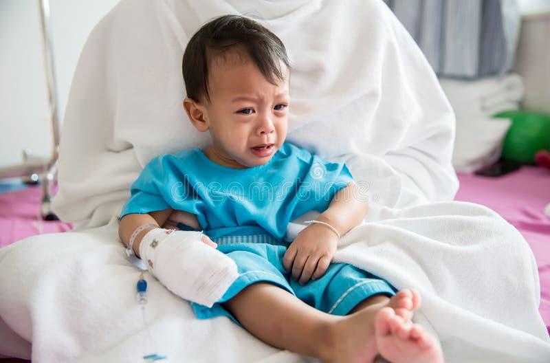 儿童病症 贴在静脉内管的小婴孩患者的手在医院病床上 小病残和哭泣在妈妈 图库摄影
