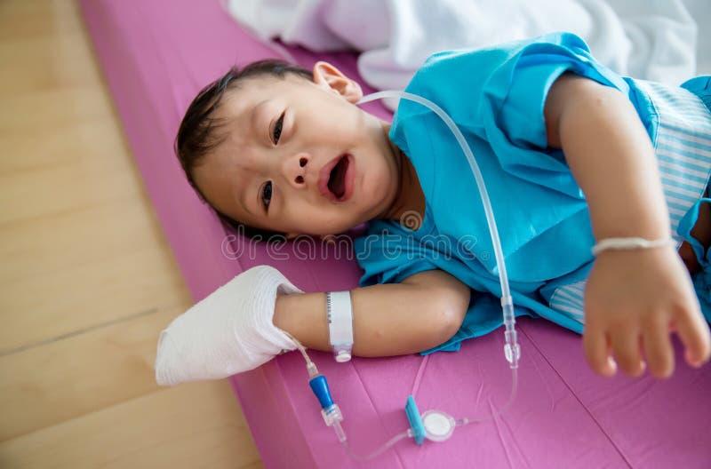 儿童病症 贴在静脉内管的小婴孩患者的手在医院病床上 小病残和哭泣在妈妈 免版税库存照片