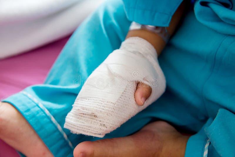 儿童病症 贴在静脉内管的小婴孩患者的手在医院病床上 库存图片