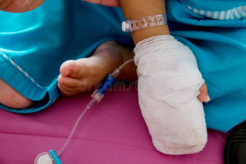儿童病症 贴在静脉内管的小婴孩患者的手在医院病床上 免版税图库摄影
