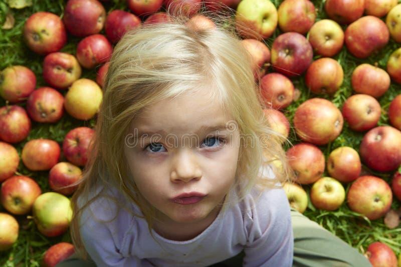 儿童白肤金发的女孩画象有苹果背景 免版税图库摄影