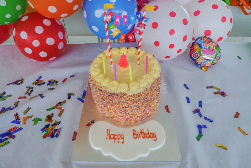 儿童的与在五颜六色的多斑点的轻快优雅前面被设置的蜡烛的生日蛋糕 免版税库存图片