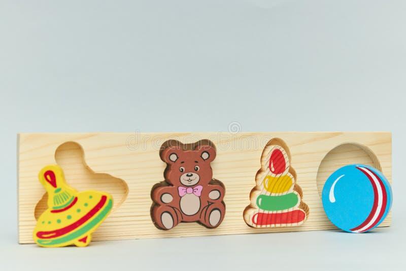 儿童的五颜六色的木玩具形象背景孩子的在轻的背景 垂直的看法特写镜头 免版税库存图片